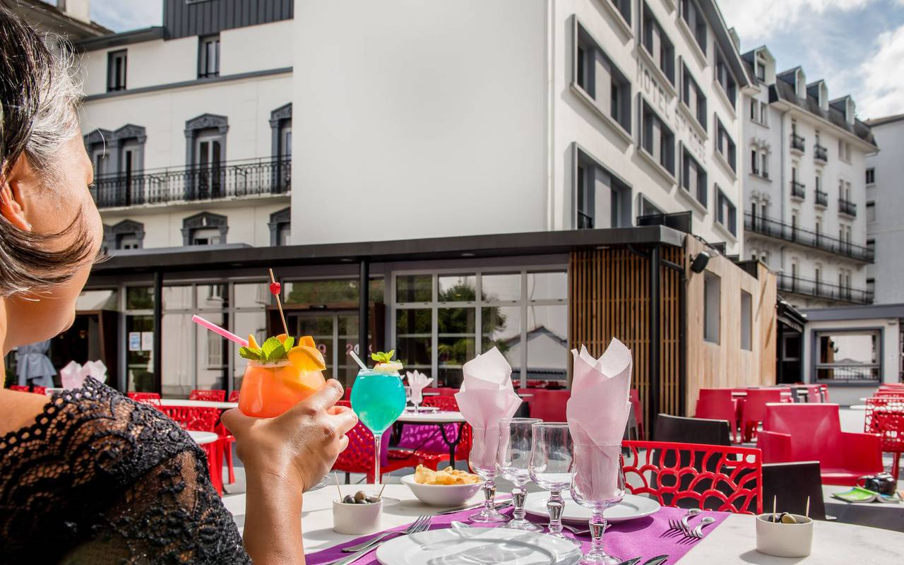 Woman drinking a cocktail on the terrace, restaurant buffet Lourdes, hotel Sainte Rose